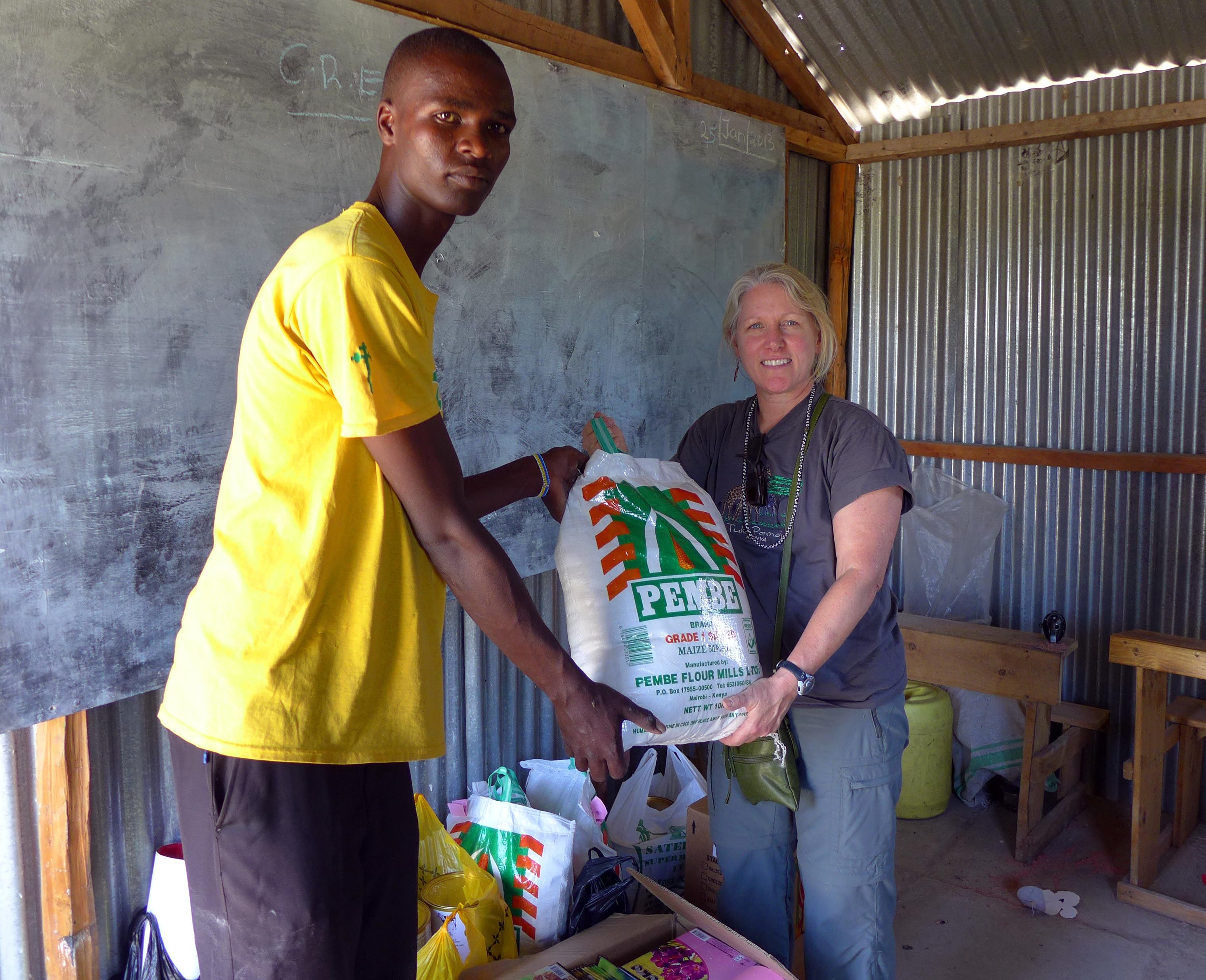 Karen and one of the PCDA teachers with a bag of maize for porridge