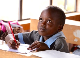 Maasai child working on a letter